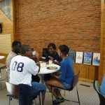Students eating pizza on the hightop tables